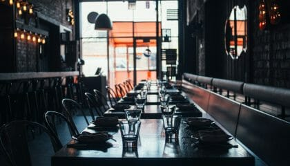 A dimly lit restaurant that has tables set in the cool and warm light.